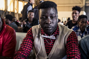 Mustafa Zacharia (26), a migrant from South Sudan, waits among a group of migrants at Tripoli's airport from where they are due to be flown to an UNHCR (United Nations High Commissioner for Refugees)...