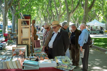 People looking through the books being sold from a stall at the Saturday flea market.