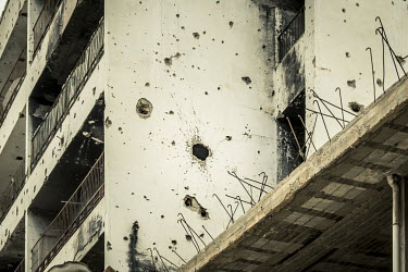 A building riddled with bullets holes and shrapnel marks from the revolution of 2011 and the civil war of 2014.