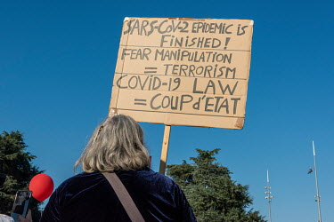 A conspirarcy theorist holds a placard during an anti-mask demonstration that attracted approximately 1,000 people to the Place des Nations in front of the United Nations building. Most were unmasked...