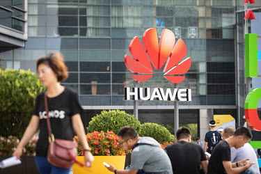 Visitors, waiting outside before entering the Huawei Connect 2017 conference, sit near a Huawei company logo.