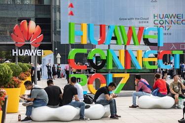 Visitors, waiting outside before entering the Huawei Connect 2017 conference, sit near a Huawei company and exhibition logo.