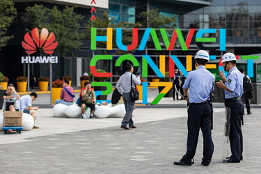 Two police officers stand guard as visitors, waiting outside before entering the Huawei Connect 2017 conference, sit near a Huawei company and exhibition logo.