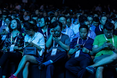 Attendees check their smartphones ahead of the keynote address at the Huawei Connect 2017 conference.