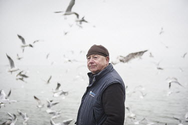 Paul Gilson, who runs a fish processing business in the town, looks out to sea as seagulls flock around fisherman Richard Eaves's trawler. The boat's crew unloaded around 100 boxes of sprat, caught in...