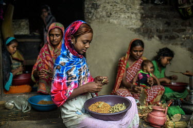 Payal Khatoon (11) (nearest camera) makes bidi (cigarettes) with her family, including her mother and grandmother, at a small house in bidi worker's colony in Aurangabad in Murshidbad district. Payal...
