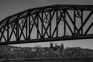 A steel bridge near a former steel mill on the banks of the Monongahela River in the Rankin district.  The population of Pittsburgh, the urban area that Rankin is a part of, has halved since its 1960s...