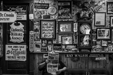 A man sits in front of a wall decorated with old pictures reading a newspaper as he waits to get a haircut at a barber's shop in Shenandoah, a city in the coal mining region of Pennsylvania.