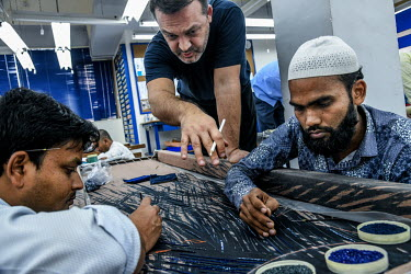 Maximiliano Modesti (centre) demonstrates a design to one of his highly skilled staff who are employed to embroider beads and sequins to fabrics in Modesti's factory in Lower Parel. Maximiliano Modest...