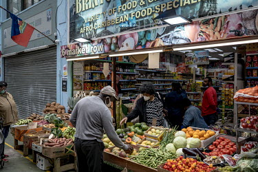 Shoppers select fruit and vegetables being sold from a specialist Caribbean grocery shop in Brixton Village covered market.