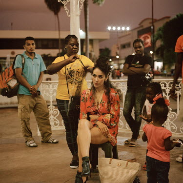 Senji (28), a migrant from Haiti, makes a little money by plaiting (braids) extensions into the hair of Claudia Garcia, a Mexican tourist visiting Tapachula. Senji lived in Brazil for five years with...