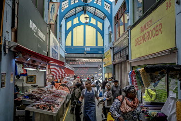 Shoppers at a fishmonger, butcher and other stalls in Market Row, part of Brixton Village covered market.