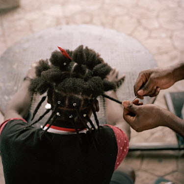 Two Haitian migrants twist each other's hair into plaits (braids) while spending time in a city park. Following pressure in July 2019 from the US government the Mexican authorities stopped issuing tra...