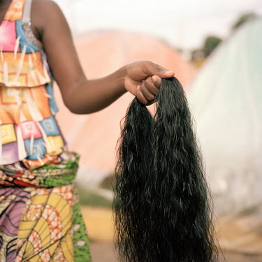 An Angolan migrant woman holds a bunch hair she will use to make extension plaits (braids). Following pressure in July 2019 from the US government the Mexican authorities stopped issuing transit visas...