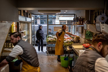 Customers wait outside as Brendan O'Sullivan works on their order as his sons Dan and Marcus prepare fish at the back of the Fin and Flounder fishmongers in Hackney, east London. The shop is now offer...