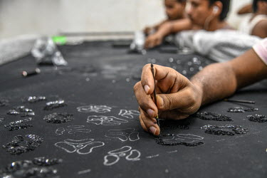 Labourers at an embroidery subcontractors attach sequins and beads to fabrics in a small factory housed in a residential block. The factory does not adhere to the Indian government's Factory Act or em...