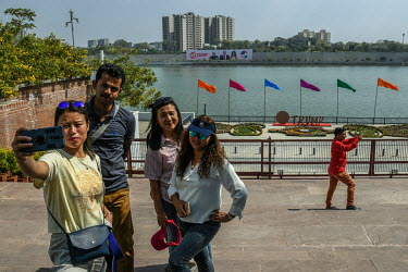 People take selfie photographs on the banks of the Sabarmati River near the Gandhi Ashram (Sabarmati Ashram), one of the sites that US President Donald Trump was due to see during a state visit to Ind...