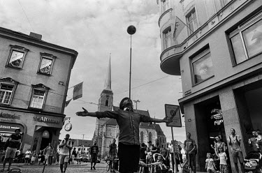 A street performer balances a ball on a pole during his act taking place near the Namesti Republiky (Republic Square).