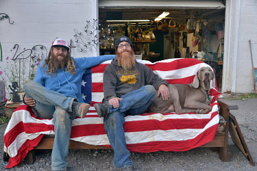 Michael Miller (Left, 37) and his business partner Kelly Howell (46) with their dog Zeus outside the second hand (thrift) store in McConnellsburg that they co-own. Both men say they will not vote in t...