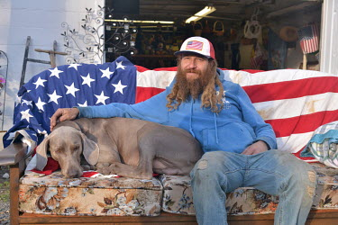 Michael Miller (37), who says he was a Donald Trump supporter but will not vote in the 2020 presidential election, sits with a dog on a sofa draped with the Stars and Stripes outside his thrift (secon...