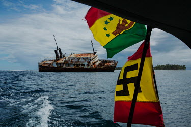 A Guna flagged boat passes alongside a ship stranded on the reefs of the San Blas Archipelago. The Naa Ukuryaa is a pre-Nazi swastika symbol used by the indigenous Guna People.