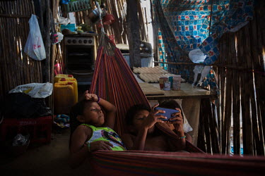 Two Guna children share a hammock and play games on a mobile phone inside a house on the island of Carti Sugdub in the San Blas archipelago. Islands in the San Blas archipelago are suffering from dest...