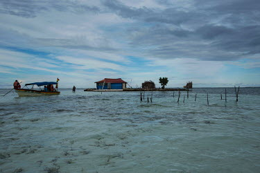 A boatman attempts to approach a house built on a small island in the San Blas Archipelago protected from the sea by a coral wall. Islands in the archipelago are suffering from destructive tidal surge...