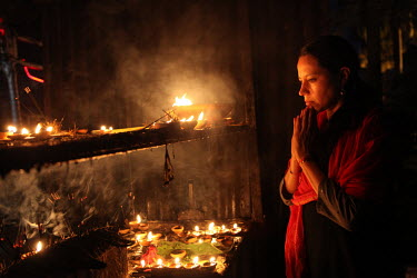 A female pilgrim prays beside incense and votive candles in the Devi Dol Shiva Temple.