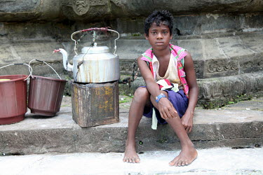 A boy beging on the steps of a Shiva Temple, sitting next to a tea pot.
