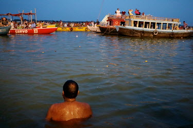 A man swims in the River Ganges as people crowd into boats for a festival.