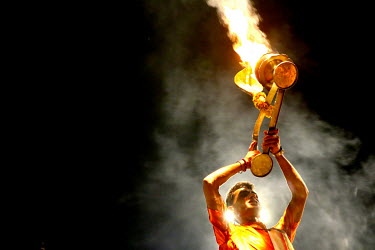 A man raises a burning flame during a ceremony on the River Ganges.