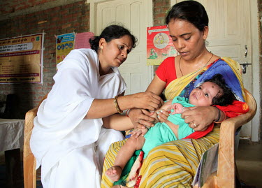 A health worker gives a baby an injected vaccination during during a village health and nutrition day.