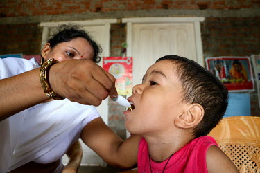 A health worker gives a child a dose of vitamins during during a village health and nutrition day.