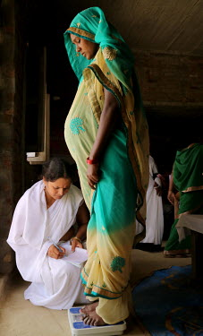 A health worker records the weight of a pregnant woman during an ante-natal check up.