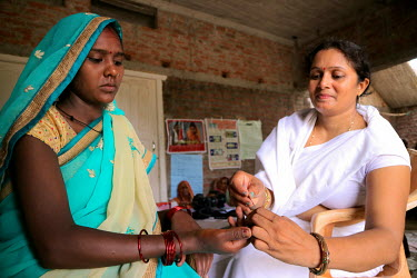 A health worker takes a pin prick blood sample from a pregnant woman during an ante-natal check up.