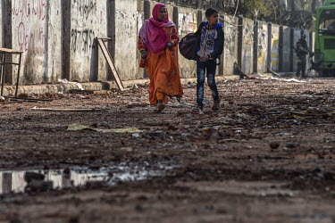 A woman and a boy walk along a street strewn with debris following rioting in Mustafabad. When rival groups, largely split between Hindus and Muslims, began protesting for and against the new Citizens...