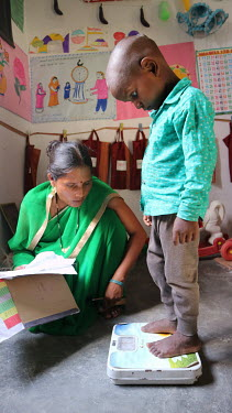A health worker weighs a boy during a growth monitoring session at a village health centre.
