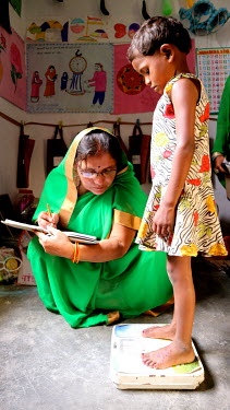 A health worker weighs a girl during a growth monitoring session at a village health centre.