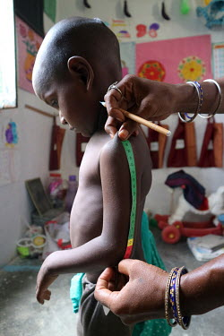 A health worker measures a boy during a growth monitoring session at a village health centre.