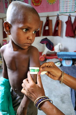 A health worker carries out a MUAC test on a boy during a growth monitoring session at a village health centre.