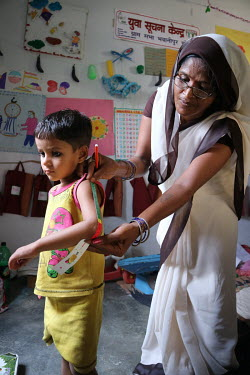 A health worker measures a child during a growth monitoring session at a village health centre.