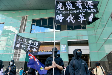 Protestors in black wave a flag with the slogan 'Free Hong Kong, Revolution Now!' as people gather at a metro station at the start of a rally in support of the 'HK 12' (12 young HK activists who were...