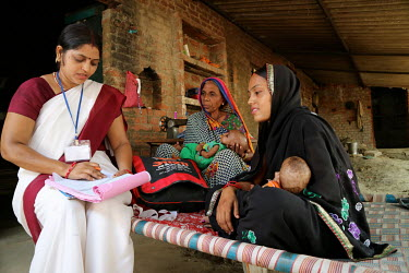 Health worker Asha visits a home in Shahpur- Khajuraul and talks with the mother, and grandmother, of two new born babies as she takes their measurements during a growth and development check up.