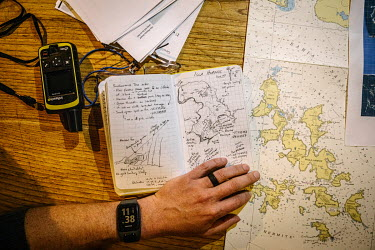 Expedition leader and scientist, Brian Buma, looks at a map of Cape Horn Island (Isla Hornos) he has drawn in a sketchbook. Buma, a specialist in high latitude temperate rainforests, is leading a team...