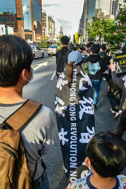 A protestor draped in a flag with the slogan 'Free Hong Kong, Revolution Now!' as a crowd, estimated at between 500-1000 people, march through central Taipei in support of the 'HK 12' (12 young HK act...