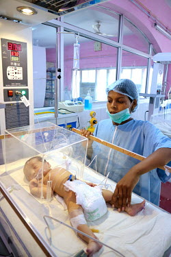 A health worker checks a premature baby who is undergoing treatment in the Sick New Born Care Unit at the Virangna Avanti Bai District Women's Hospital.