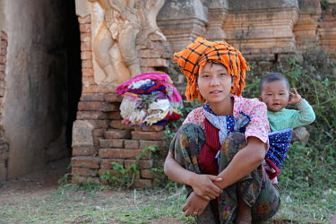 A young woman, her baby strapped to her back, sells scarfs to the tourists at the Nga Phe Kyaung Monastery.