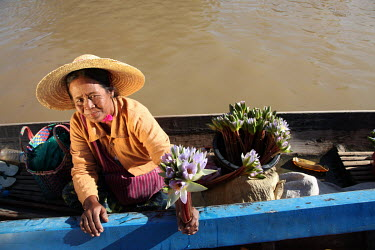 A woman selling lotus flowers from her boat floating on Inle Lake.