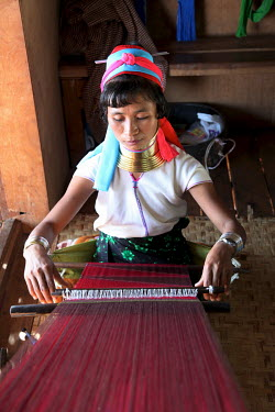 Women from the Kayah (Red Karen, Padaung) ethnic group weaving silk scarfs on hand looms.