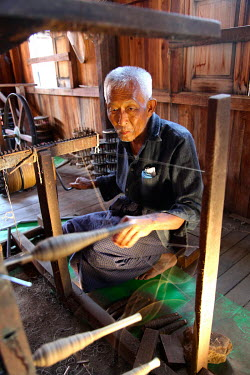 A man spinning silk thread.